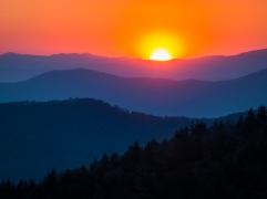 The sun sets in dramatic fashion over blue-tinged layers of mountains along the Blue Ridge Parkway