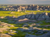 Evening sun highlights yellow sweet clover coloring the valleys of the Badlands in South Dakota