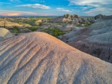 The last light of day falls across a grand view of textured hills in the Badlands, South Dakota