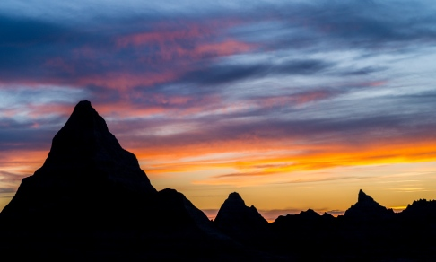Jagged peaks are silhouetted against a colorful sunset sky in Badlands National Park, South Dakota