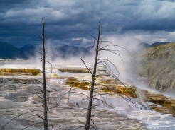 Late evening sun highlights the steaming terraces set against storm clouds