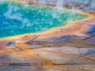 Steam rises off the rainbow-colored cGrand Prismatic Spring evoke an alien landscape