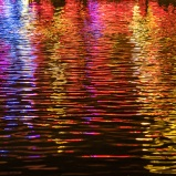 Neon lights reflect off Echo Lake at night at Disney World's Hollywood Studios
