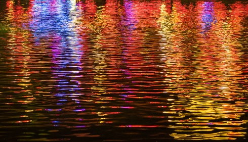 Neon lights reflect off Echo Lake at night at Disney World's Hollywood Studios