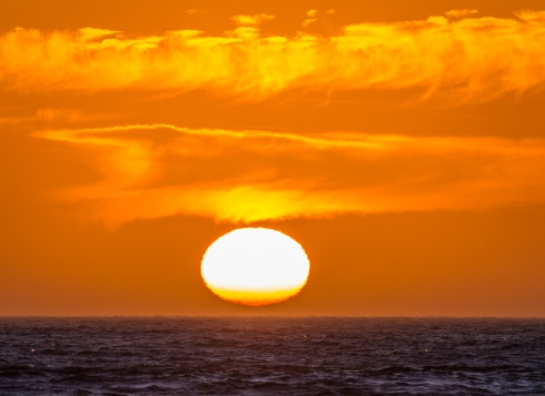 A telephoto lens gives a magnified view of the setting sun north of Florence, Oregon