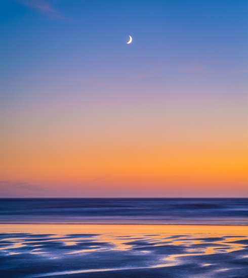 A sliver of moon highlights a coastal composition made in the waning light of dusk