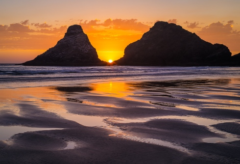 The setting sun disappears between seastacks at the Haceta Head lighthouse beach