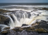 Waves at high tide are swallowed up into a large hole on the rocks near Cape Perpetua