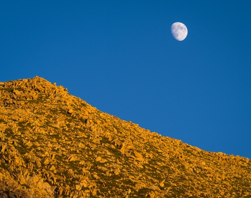 A bright moon rises over a rugged peak in Lee Vining Canyon