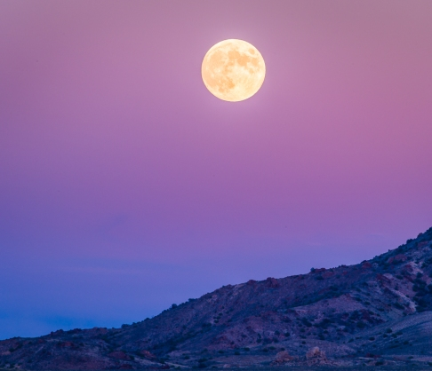 A full moon rises above Nevada desert mountains at dusk