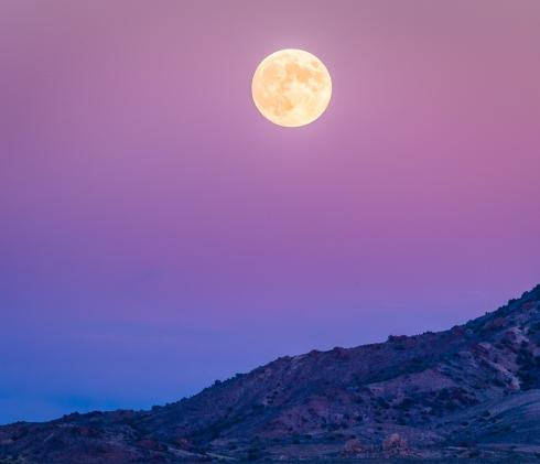 A full moon rises above Nevada desert mountains at dusk