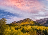 Clouds reflect warm light at sunset over Mount Timpanogos draped in golden aspens