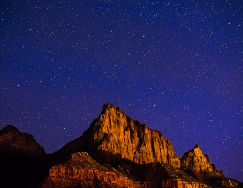 The Watchman peak glows under a starry sky in Zion National Park